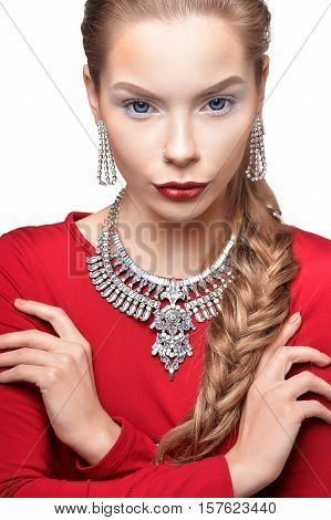 Portrait of beautiful young woman with stylish make up, elegant jewelry and in red dress with her arms crossed looking at camera