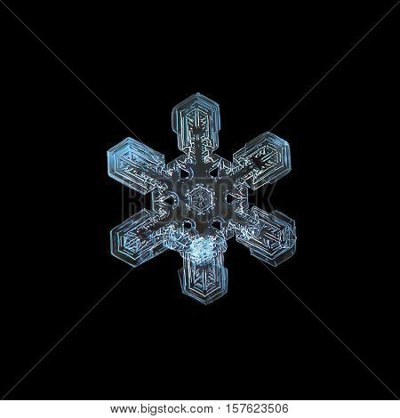 Snowflake isolated on black background. This is macro photo of real snow crystal: large stellar dendrite with simple shape, but complex and beautiful inner pattern.