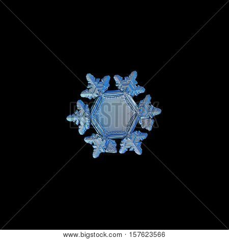 Snowflake isolated on black background. This is real snow crystal, around 3 millimeters from tip to tip, with unusual big, flat and empty central hexagon, relief outer rim and short arms with ridges.