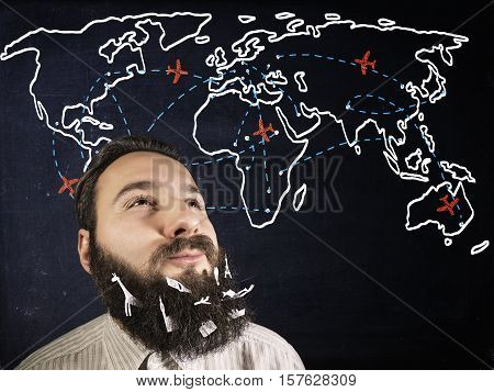 image of a smiling bearded man on blackboard background with world map painted by with chalk . Various objects - symbols of travel tourism vacation pasted in his beard. The concept of freelancing tourism vacation traveling on a dream