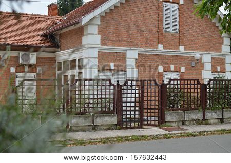 Red brick terrestrial residential house with opened gate