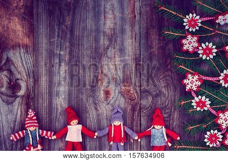 Vintage wooden Christmas background with rag dolls and decorated with fir branch