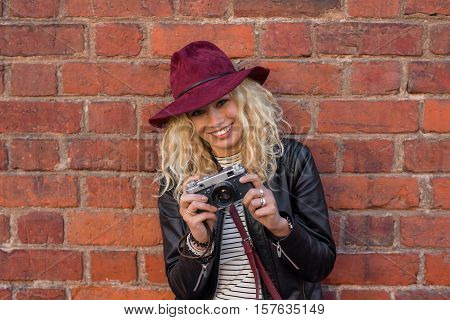happy woman taking pictures with vintage camera
