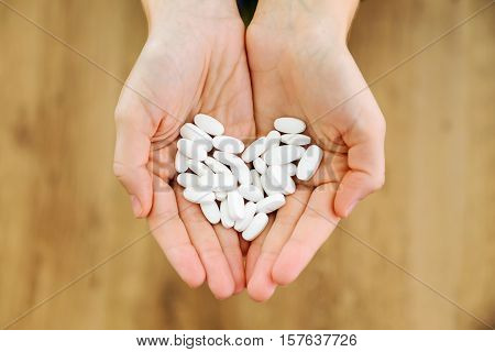Both Hands Holding Bunch Of Pills. Overdose Or Abuse Concept.