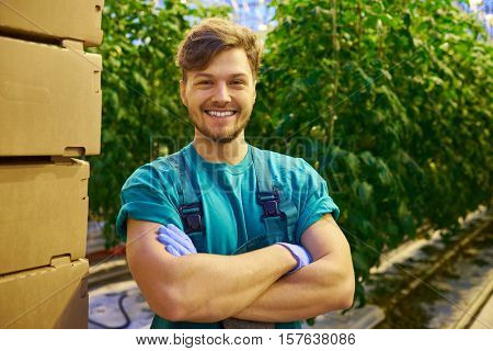 Friendly farmer at work in greenhouse.