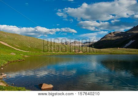 Amazing Colorado Landscape high altitude Lake sitting calm with blue reflecting off a clear sky day with plenty of sunshine in the Rocky Mountains near Telluride Colorado USA