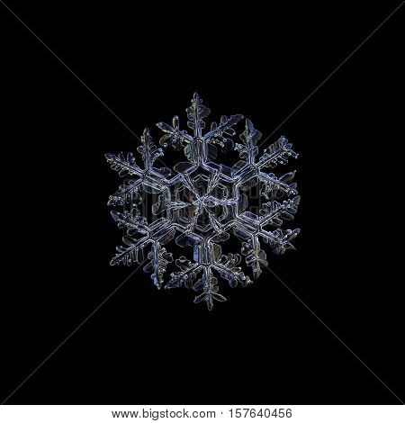 Snowflake isolated on black background. This is closeup image of real snow crystal: large stellar dendrite with ornate arms and big central hexagon, divided by six sectors.