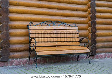 A wooden bench near the house. The forged bars on the bench lacquered wood wooden frame house figured bench handmade. A cozy place in a private house rural village.