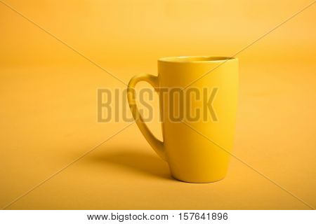 Empty yellow cup on yellow background. Yellow mug empty blank for coffee or tea.