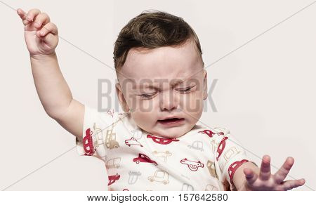 Cute baby boy crying raising his hands up. Little child in pain, suffering, teething, refusing and crying. Cute sad baby throwing a tantrum.