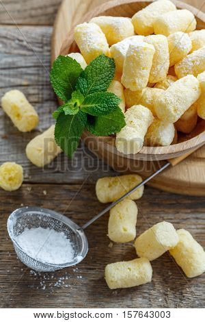 Corn Sticks In A Bowl And Sieve With Powdered Sugar.