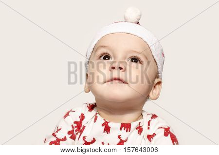 Portrait of a cute baby boy looking up thinking wearing a Santa hat. Adorable child wearing a blouse with reindeer and a red hat ready for Christmas. Funny baby face.