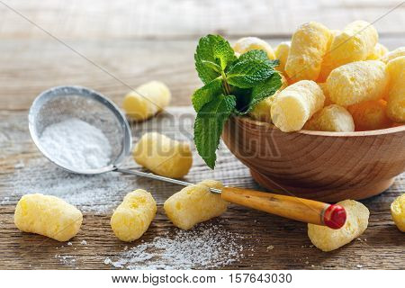Corn Sticks In A Bowl And Sieve With Powdered Sugar Closeup.