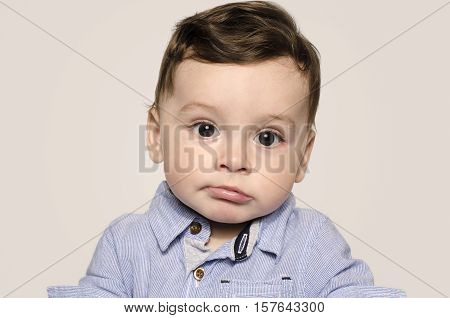 Portrait of a cute baby boy looking at camera bored. Adorable child wearing a blue shirt making cute mimic.