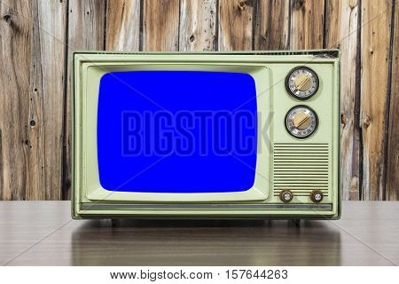 Grungy green vintage television set with wood wall and chroma key blue screen.