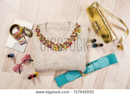 Winter sweater and accessories arranged on the floor. Woman colorful pink and blue accessories, purse, belt, bracelets and nail polish.