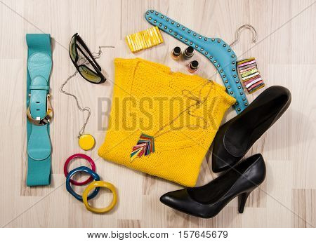 Winter sweater and accessories arranged on the floor. Woman colorful yellow accessories, high heels, sunglasses and nail polish.