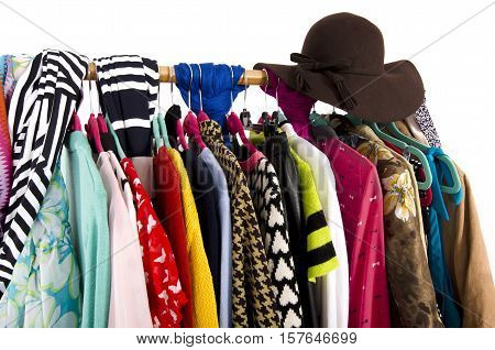 Close up on colorful clothes and hat on hangers in a store. Clothes and accessories hanging on a rack nicely arranged.