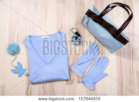 Winter sweater and accessories arranged on the floor. Woman blue and brown accessories,necklace and gloves lied down.