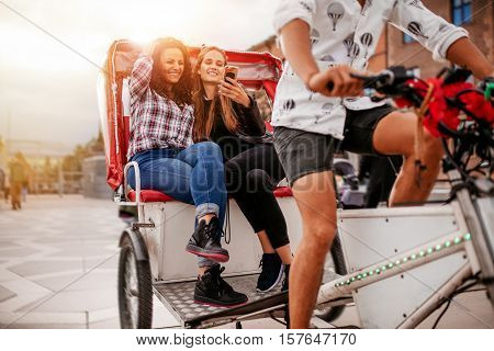 Young women sitting on tricycle and looking at mobile phone. Female friends enjoying tricycle ride on road.