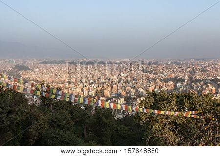 Aerial View Over The Nepalese Capital Kathmandu And Buddhist Prayer Flags From Swayambhunath Temple.