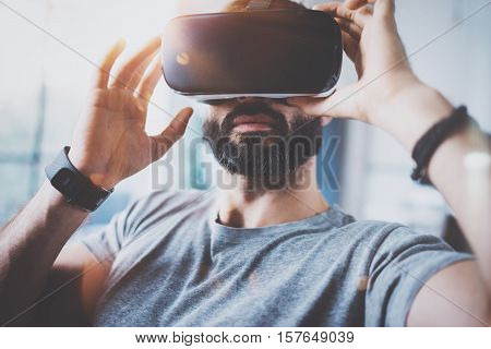 Closeup of bearded man wearing virtual reality goggles in modern coworking studio. Smartphone using with VR headset. Horizontal, blurred