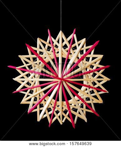 Straw star Christmas decoration on black background. Handmade colorful decor for windows, as gifts or to hang on the xmas tree, traditionally made from natural straw. Macro photo front view close up.