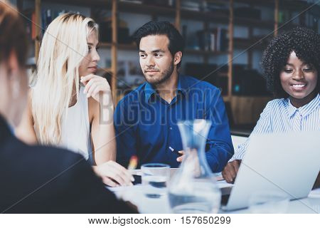 Young team of coworkers making great business discussion in modern coworking office.Hispanic businessman talking with partners.Teamwork people concept.Horizontal, blurred background