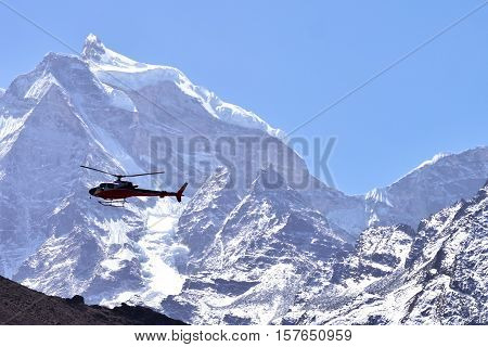 Rescue helicopter in flight over snow capped mountains