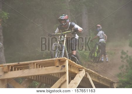 Sport race Mountain biker extreme and fun downhill track. Jumps and dirt splashes.