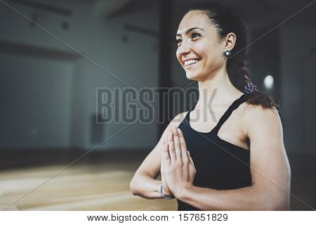 Portrait of gorgeous young woman practicing yoga indoor. Beautiful girl practice meditation asana in class.Calmness and relax, female happiness.Horizontal, blurred background