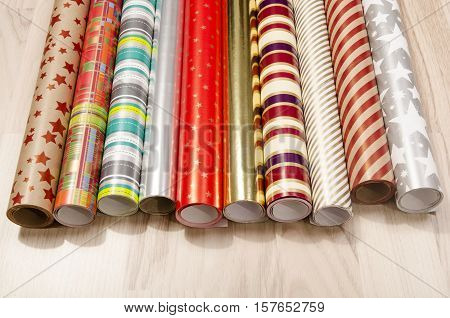 Many rolls of wrapping paper for Christmas. Colorful red, green, silver wrapping paper for presents.