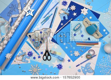 Arts and craft supplies for Christmas. Blue color paper pencils different washi tapes craft scissors wrapping paper rolls festive Xmas supplies for decoration.