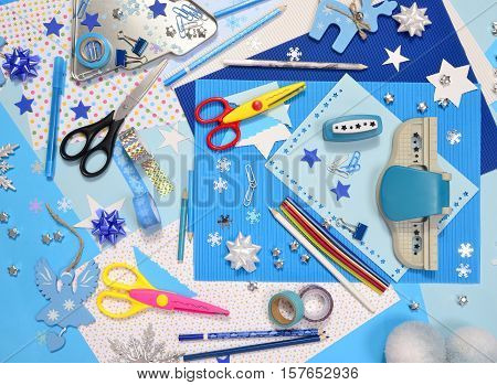 Arts and craft supplies for Christmas. Blue color paper pencils different washi tapes craft scissors festive Xmas supplies for decoration.