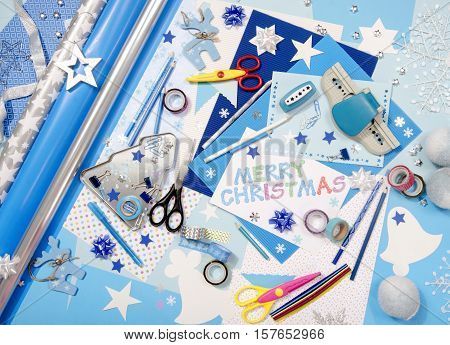 Arts and craft supplies for Christmas. Blue color paper pencils different washi tapes craft scissors wrapping paper rolls festive Xmas supplies for decoration. Merry Christmas paper sign.