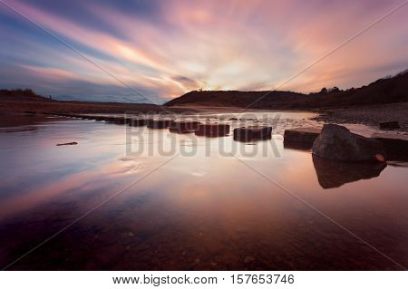 Sunset at the stepping stones that allow access to the divided beaches at Three Cliffs Bay on the Gower peninsula in Swansea, South Wales