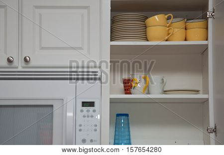 White kitchen cabinet filled with cups & plates next to a microwave