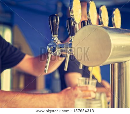 Barman hand at beer tap pouring a draught lager beer serving in a restaurant or pub.Vintage look