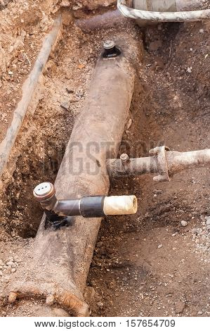 Excavation for water pipe maintenance. Laying new water pipeline and water valve in a trench.