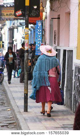 Potosí Bolivia - November 21 2016: Woman in traditional dress walks on a Monday morning in Potosí Bolivia on November 21 2016