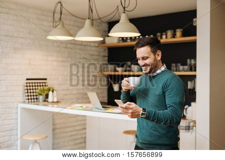 Handsome man enjoying time for internet and coffee.
