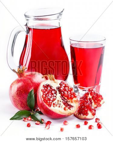 Pomegranate juice in pitcher and pomegranates on white background