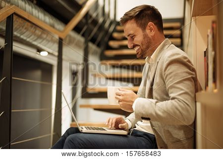 Handsome man working on a computer and drinking coffee.