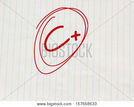 C plus (C+) grade written in red on notebook paper