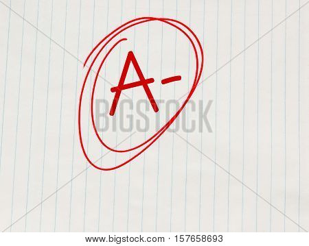 A minus (A-) grade written in red on notebook paper