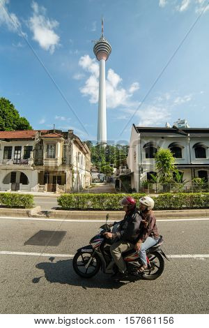 Kuala Lumpur, Malaysia - September 24, 2016: Locals drive motorbike on the street with a famous Menara KL tower at background