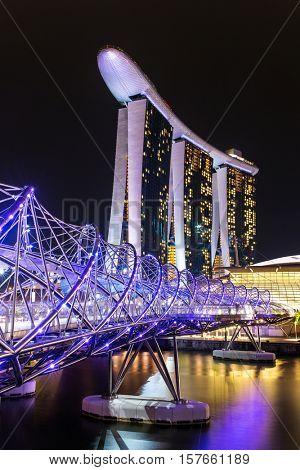 Singapore - June 24, 2016: Helix bridge and Marina Bay Sands Hotel at night in Singapore