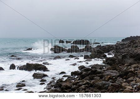 Rocky coast of New Zealand with crashing waves