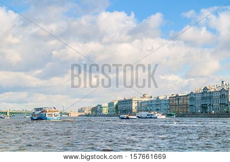 ST PETERSBURG RUSSIA - OCTOBER 3 2016. Historic buildings on the Palace embankment of Neva river and touristic sailboats floating on the water area of Neva river in St Petersburg Russia