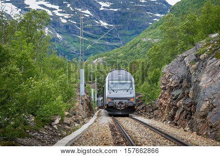 Flamsbana touristic mountain railway train at it's way to Kjosfossen waterfall. Flam, Norway.